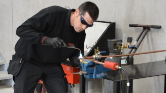 Pipeline Solutions staff member welding some industrial pipeline equipmenr