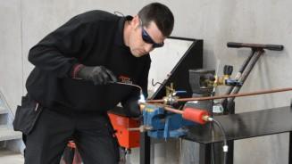 Pipeline Solutions staff member welding some industrial pipeline equipmenr